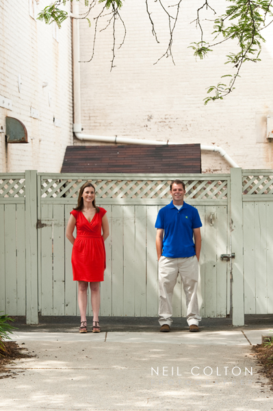 engaged couple posing againts a fence in old town alexandria
