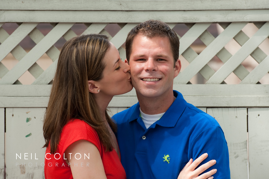 portrait of an enageged couple kissing in old town alexandria