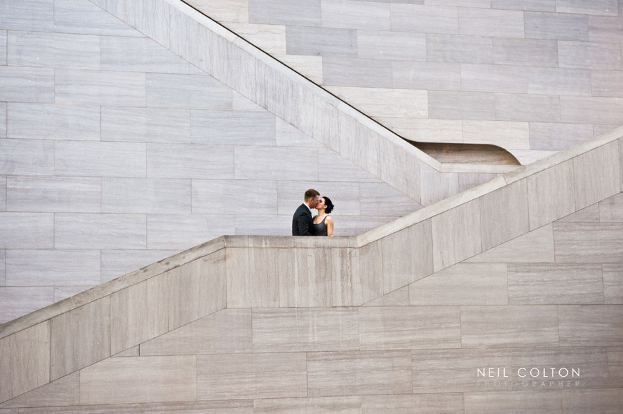 Portrait of a couple kissing in a Washington DC art gallery.