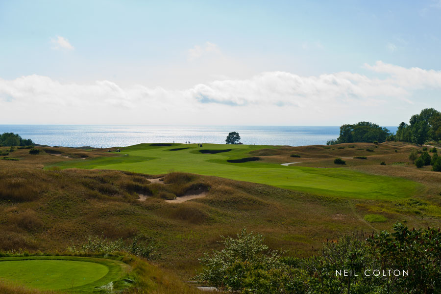 Portrait of Arcadia Bluffs golf course with golfers in the distance along Lake Michigan