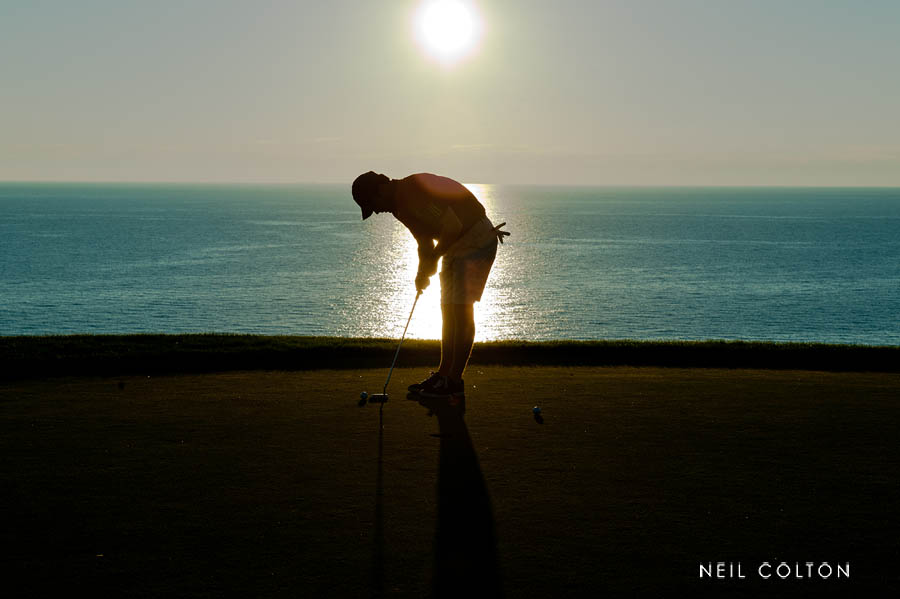 Portrait of a golfer at sunset putting as the sunsets on Arcadia Bluffs Golf Course in Arcadia MI.